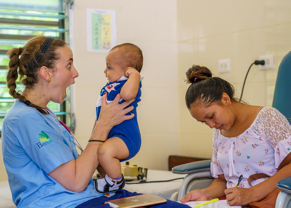nurse holding a baby and a woman filling out paperwork in the background