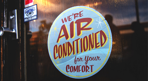 "Sign on a window that reads ""air conditioned for your comfort"""