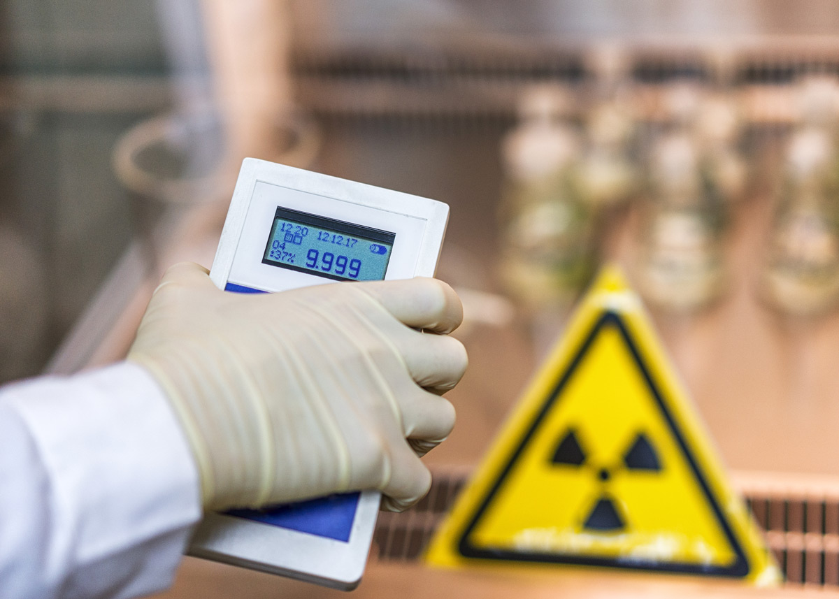dosimeter in gloved hand with a radiation sign in the background