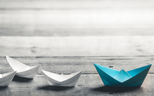 multiple paper boats, white ones following a larger blue one