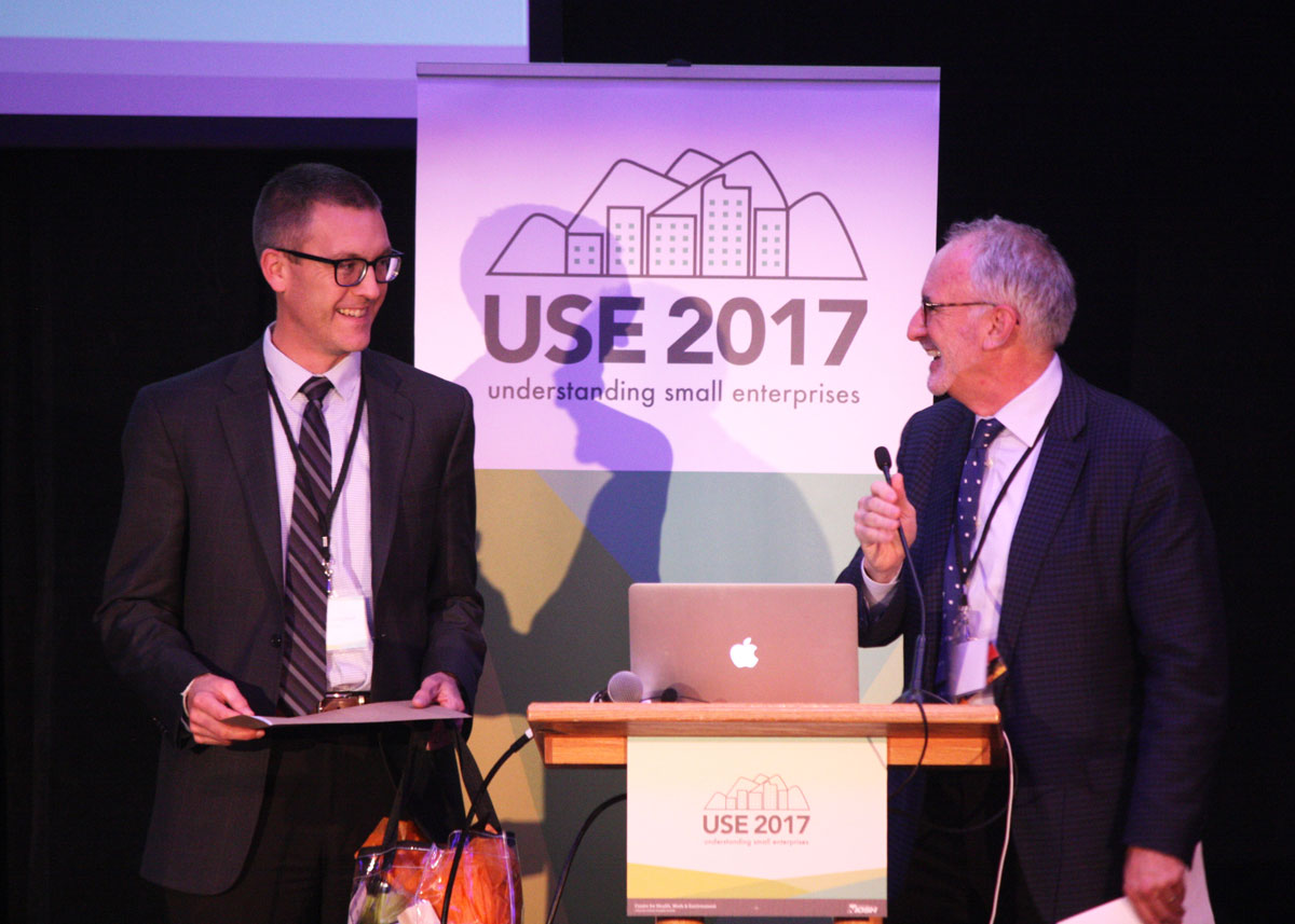 Lee Newman and Tom Cunningham on stage standing in front of a USE Conference banner
