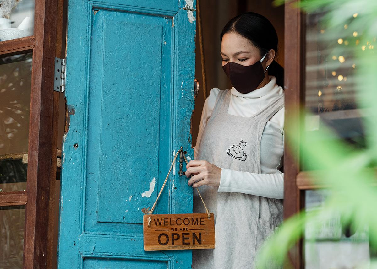 woman wearing face mask hanging open sign on business door