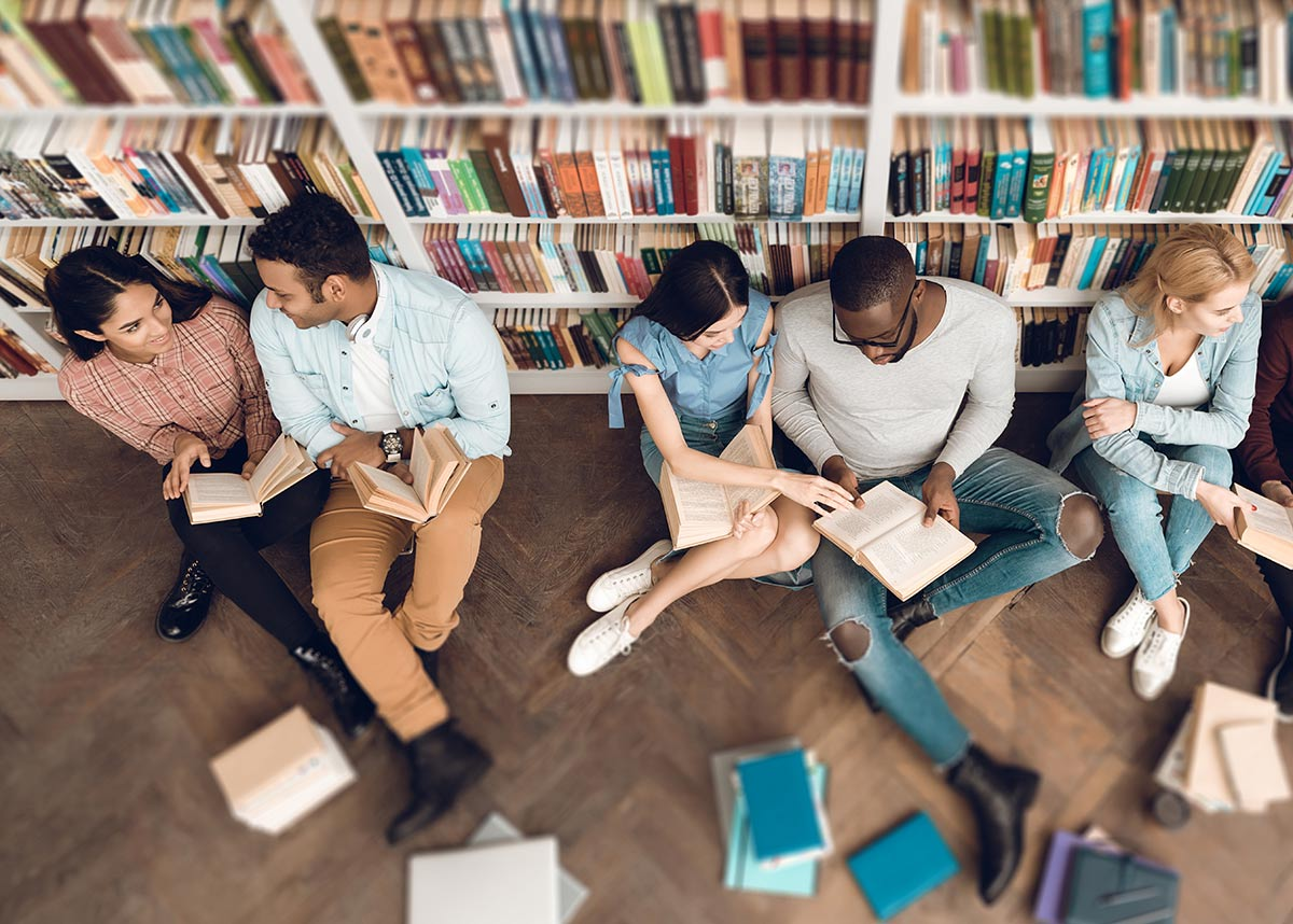 group of students reading on the floor of a library