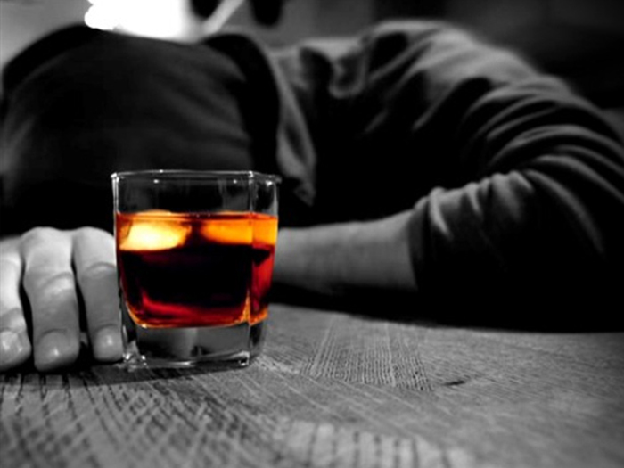 person laying on table with glass of alcohol