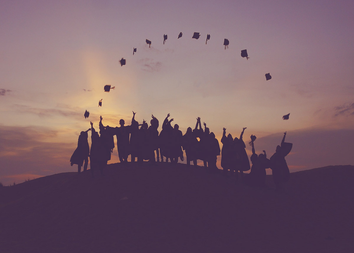 group of graduates throwing their caps in the air
