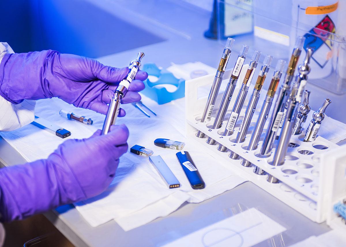 gloved hands of lab tech holding e-cigarette