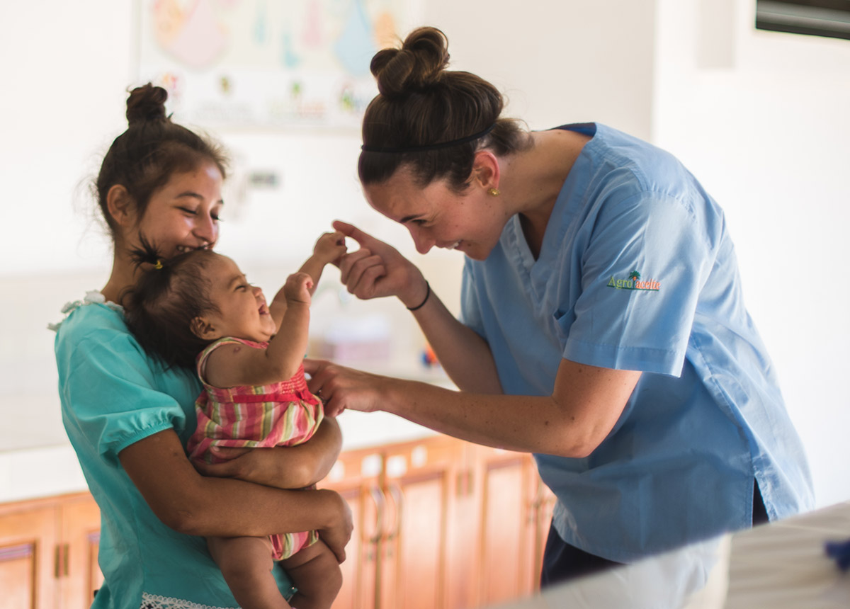 healthcare worker playing with child who is being held by a woman