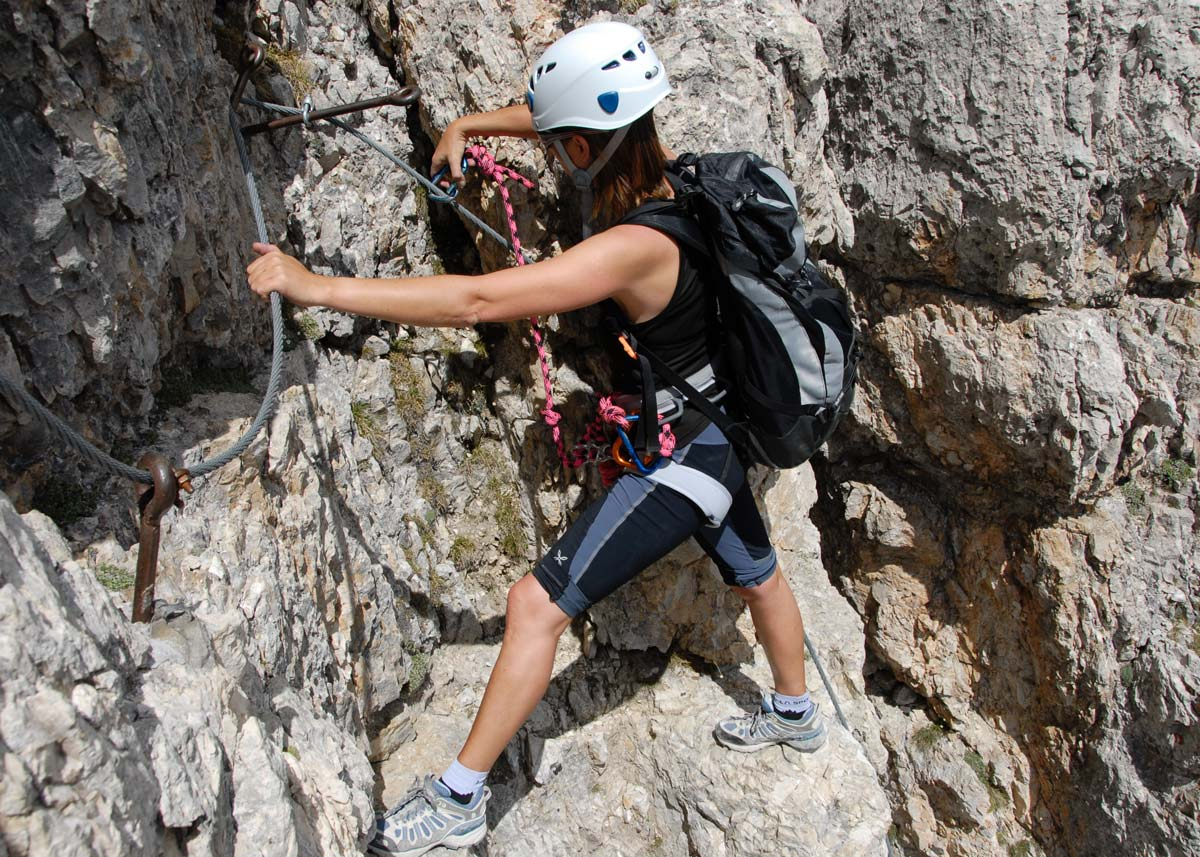 person climbing mountain with helmet and gear