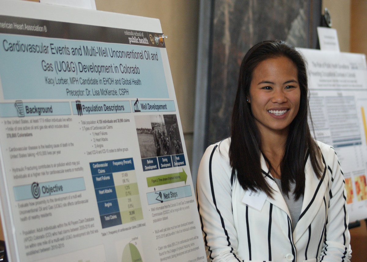 student smiling in front of her research poster