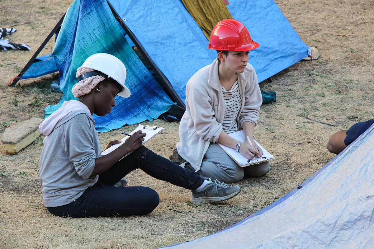 two students in hard hats taking notes at a disaster prepardness drill
