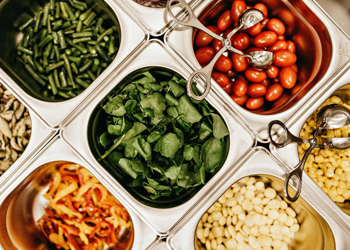 salad bar with different vegetables and tongs