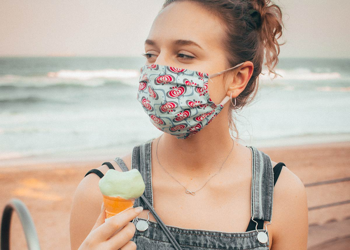 woman wearing a mask at a beach holding an ice cream cone
