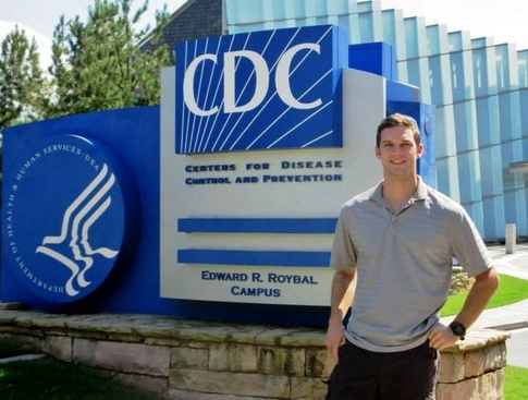 Kyle Roesler standing in front of CDC sign