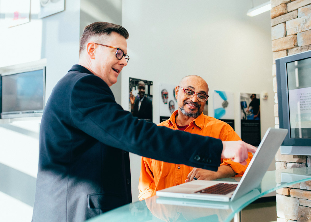 two men talking and looking at a laptop