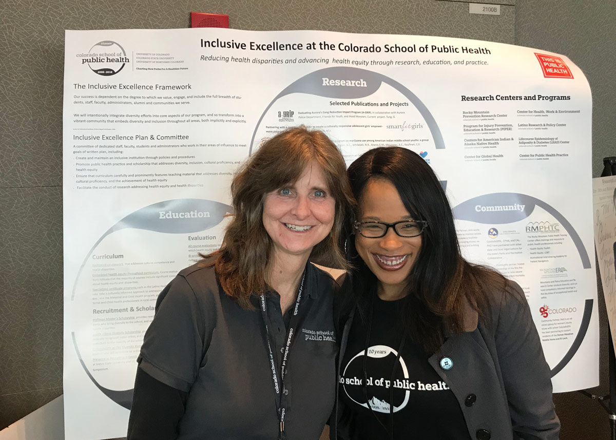 Lori Crane and Cerise Hunt in front of a research poster about inclusive excellence