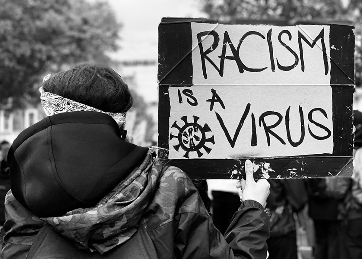 "protester holding a sign that reads ""racism is a virus"""