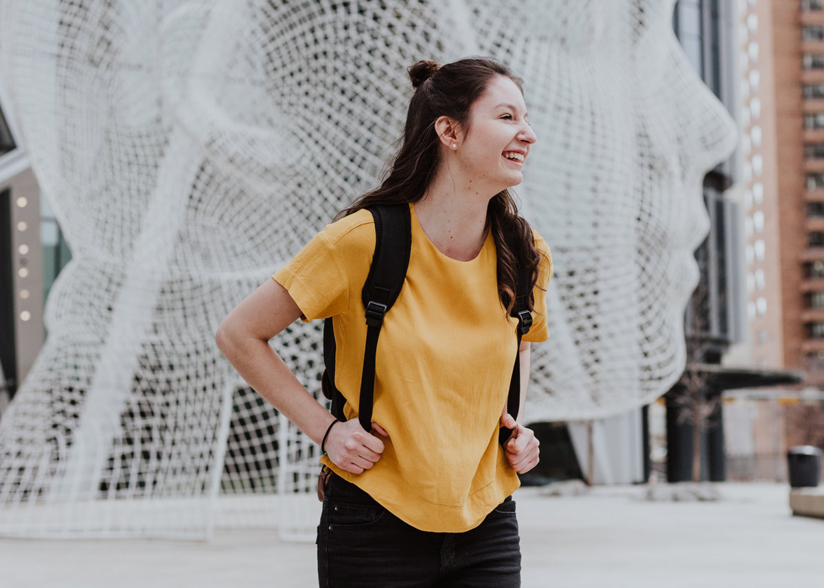 woman laughing with backpack on