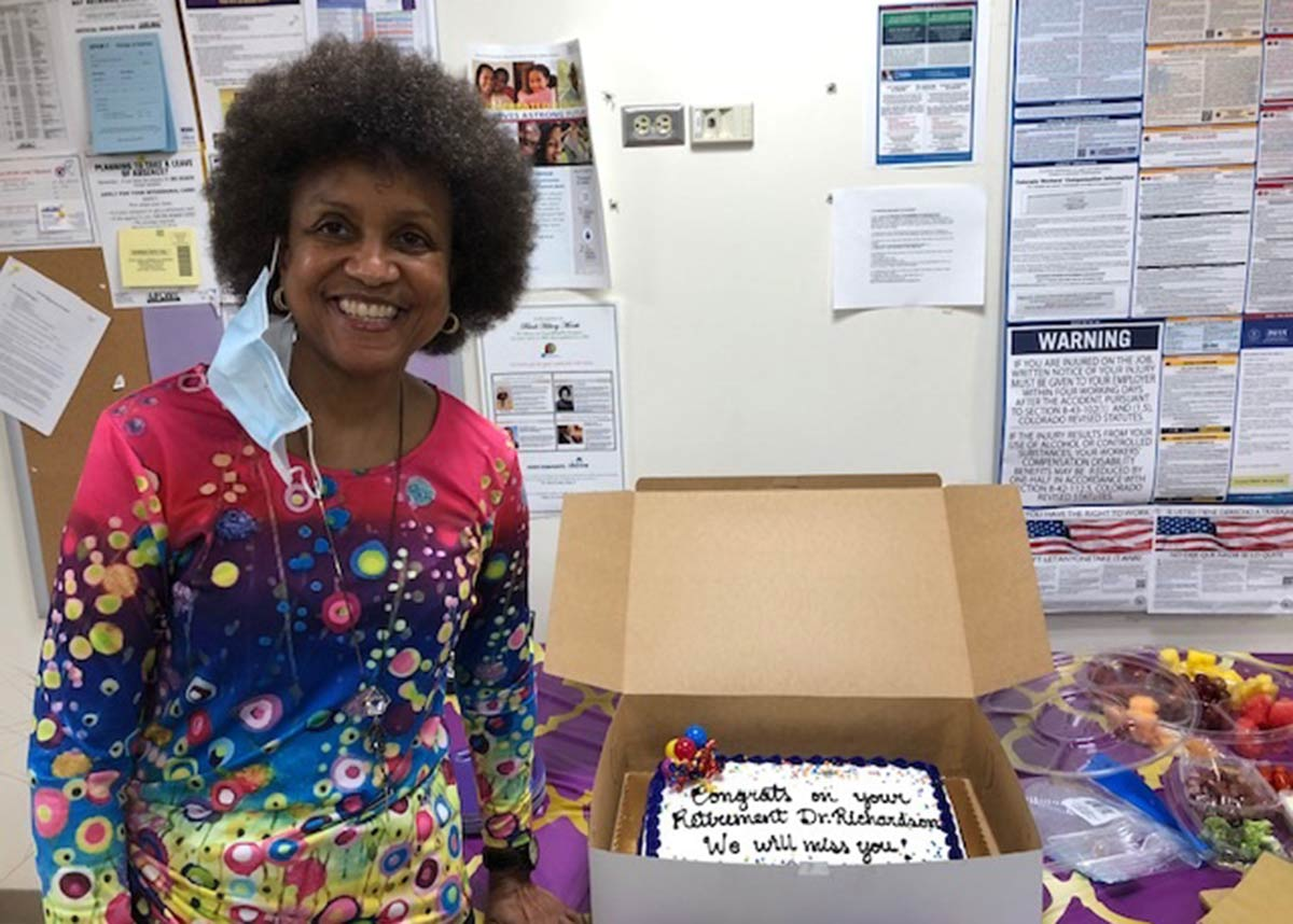 Terri Richardson smiling next to a cake