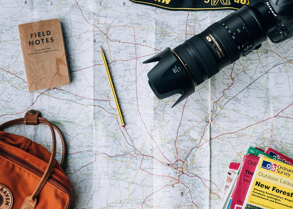 A map with a bag, notebook, camera, and travel guides on top