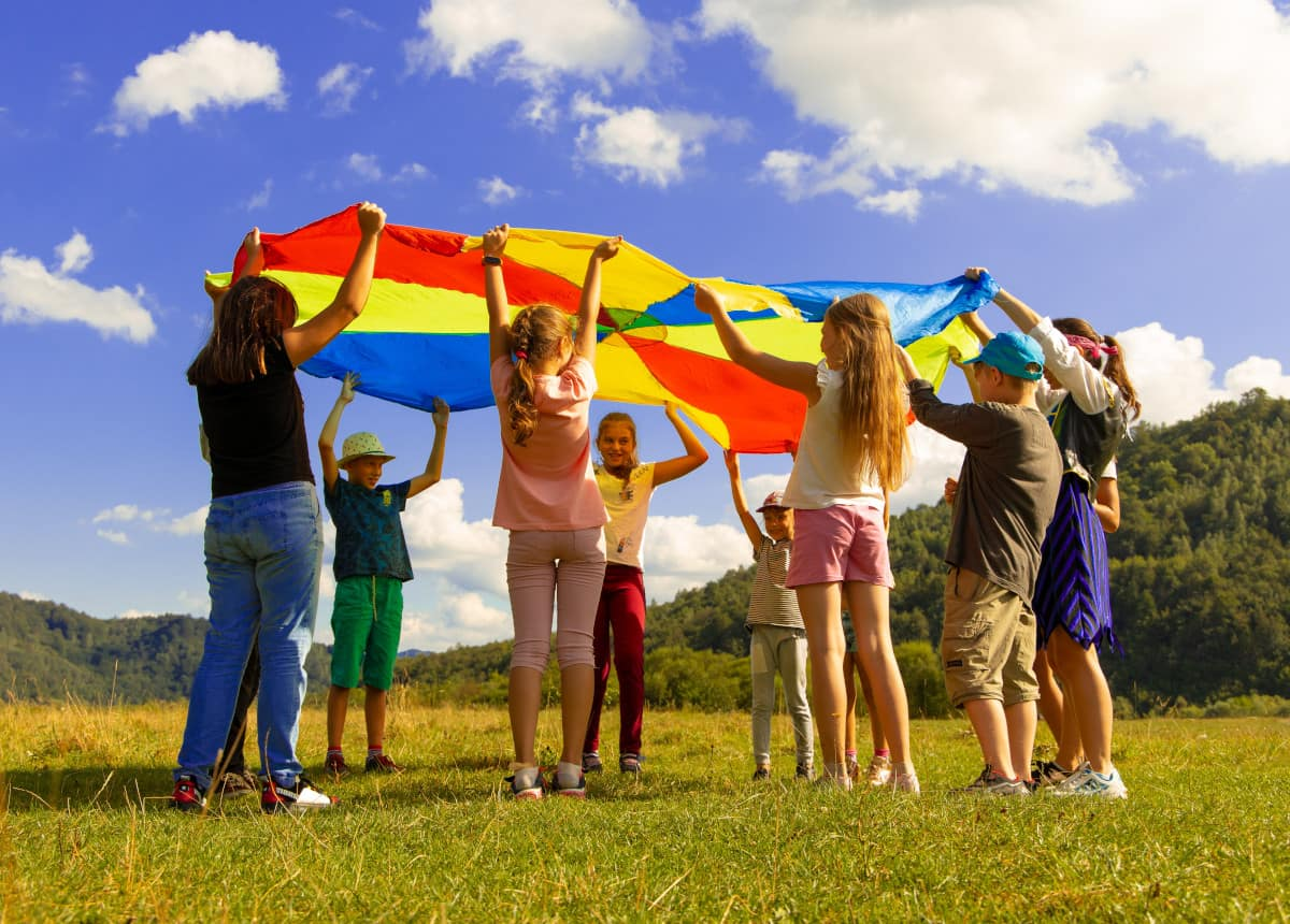 children playing with colorful parachute outside