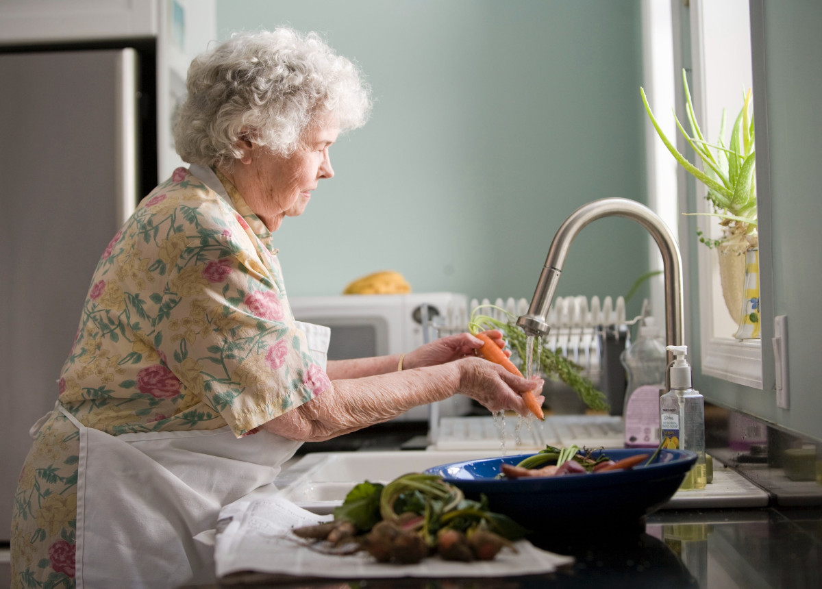 elderly woman washing vegetables