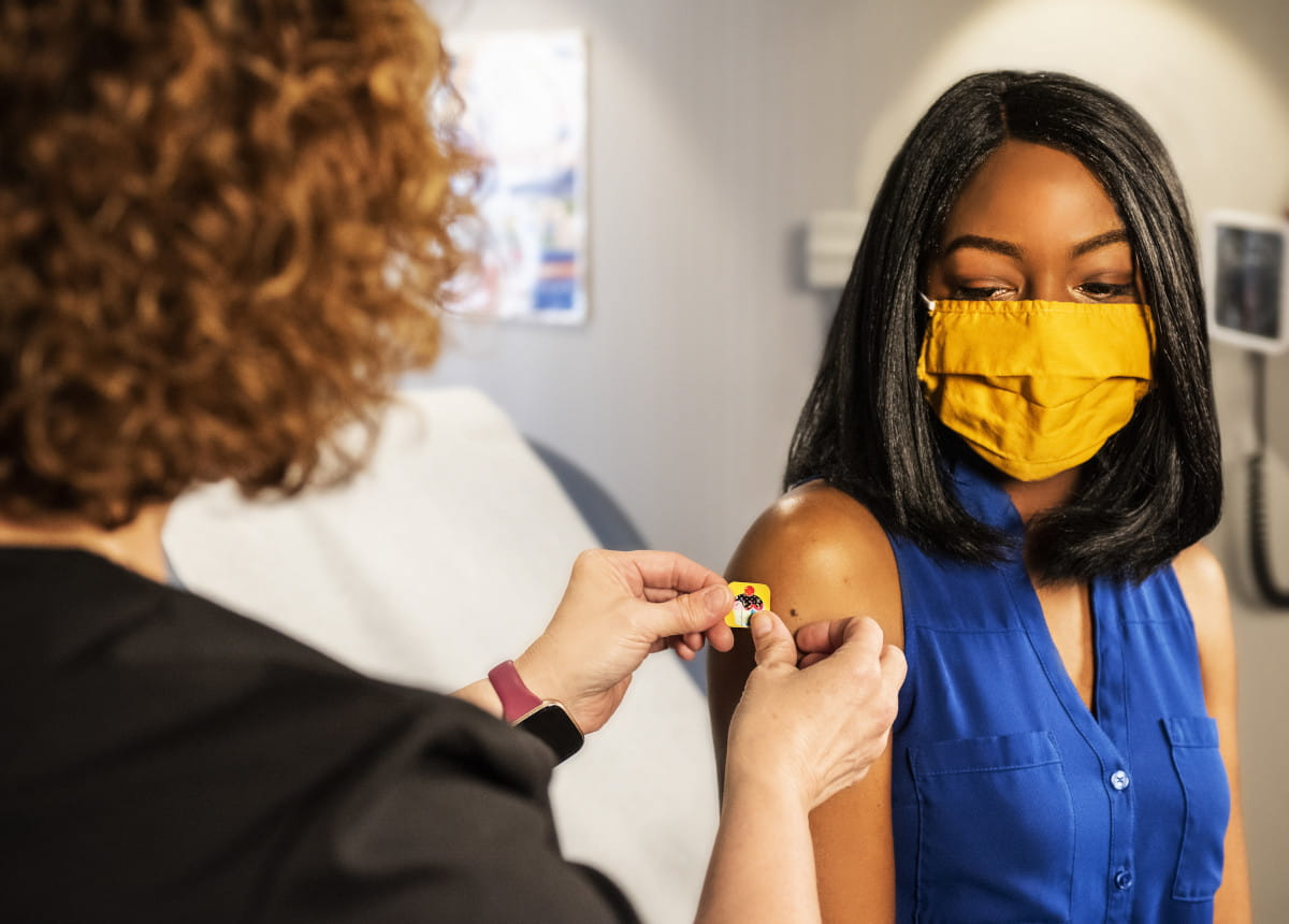 woman having bandaid put on arm after vaccination