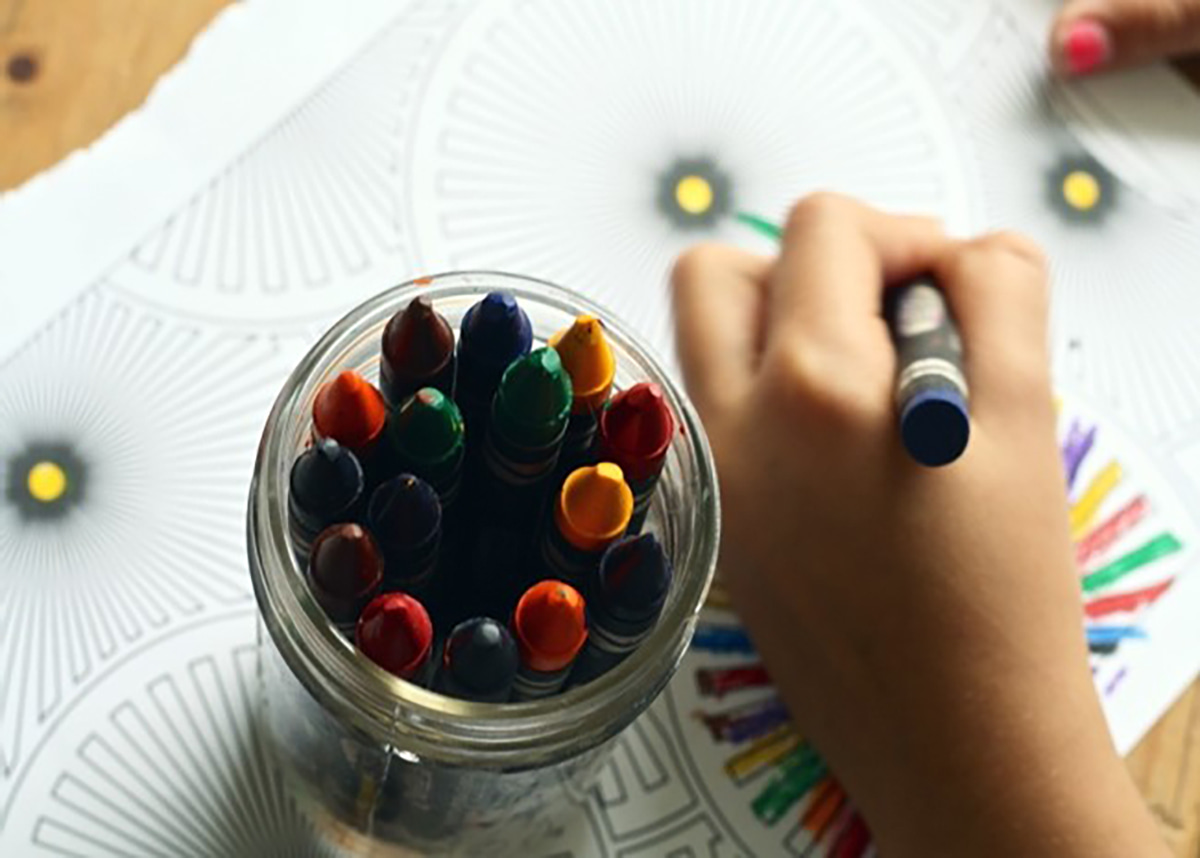 Child's hand coloring with crayons