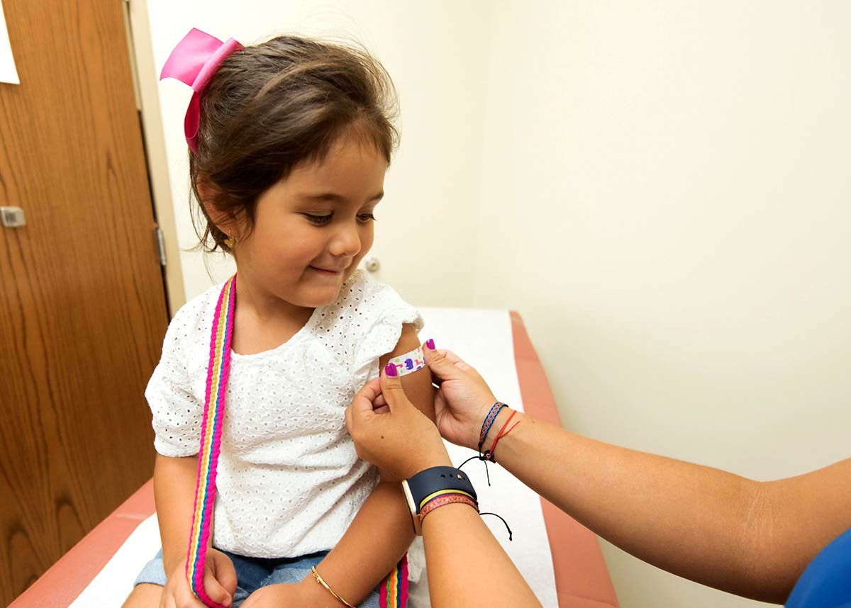 child in doctor's office getting a bandaid put on her arm
