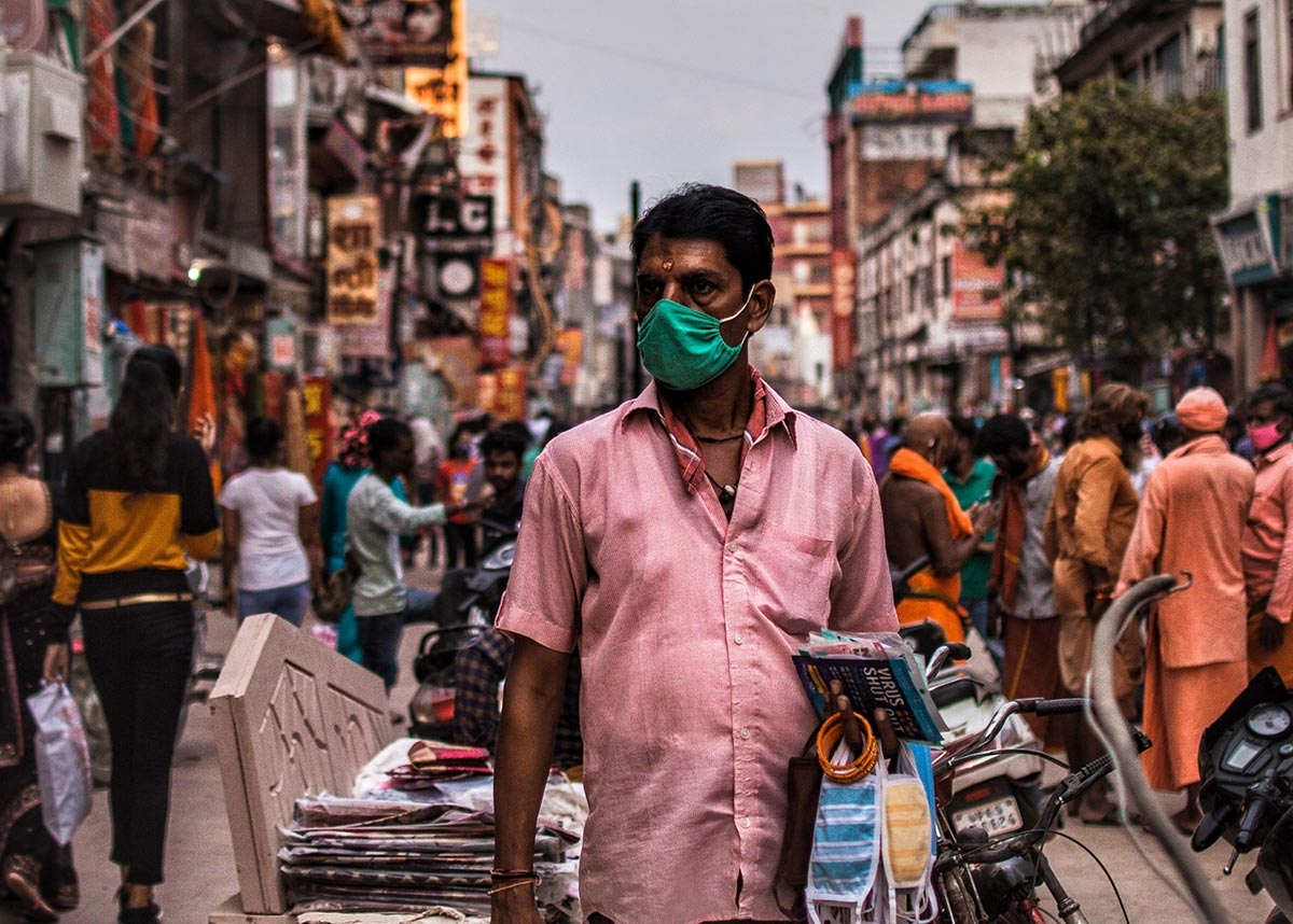 man in a mask walking through busy streets in India
