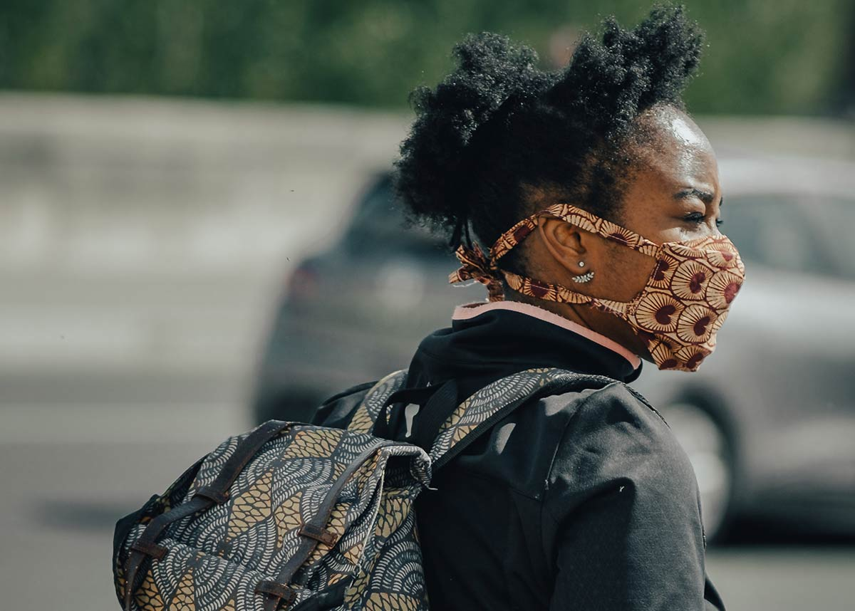 woman with a backpack and face mask on walking