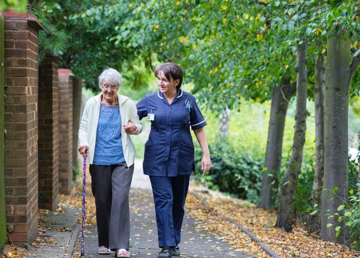 elderly woman and nurse walking down street