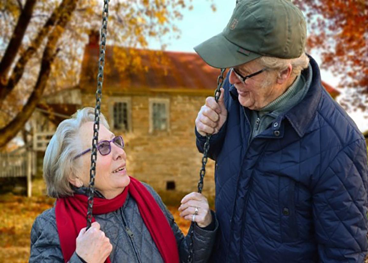 Elderly couple sitting on swings