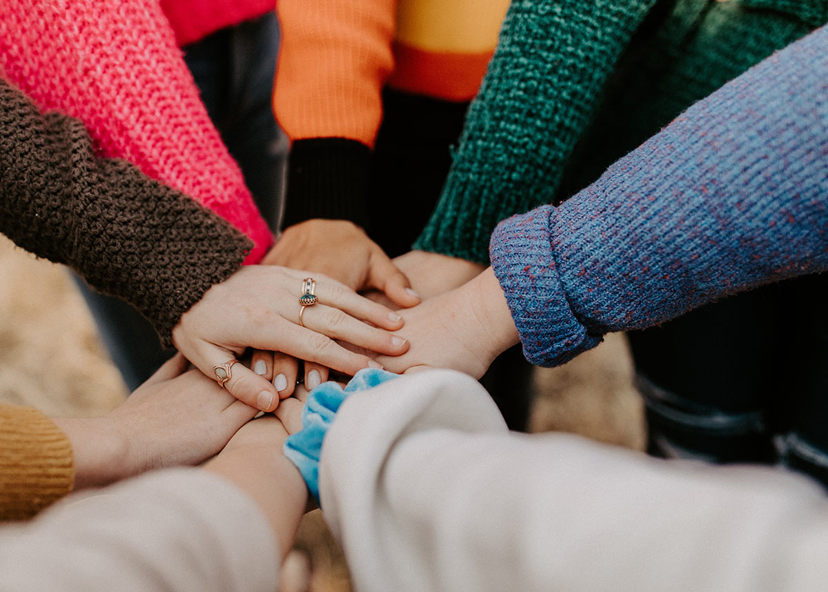 group of hands in on top of one another