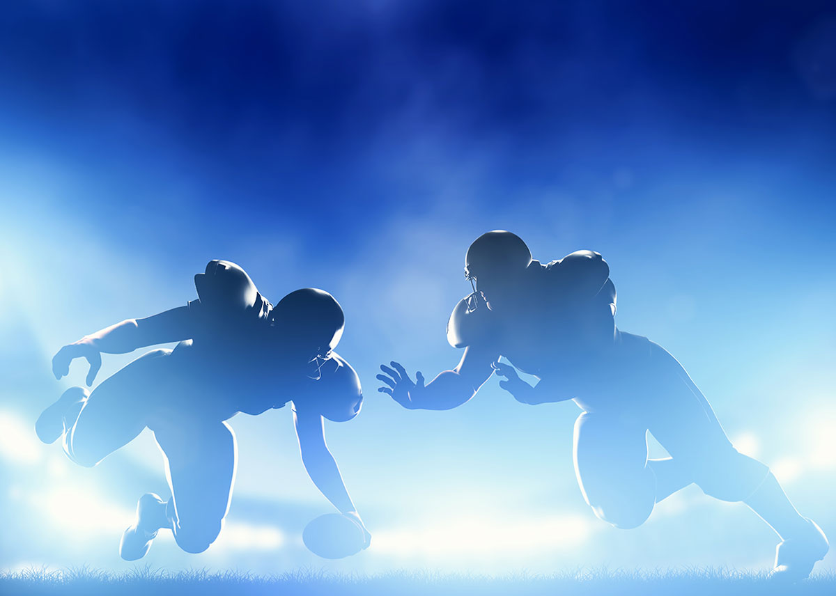 Two backlit football players