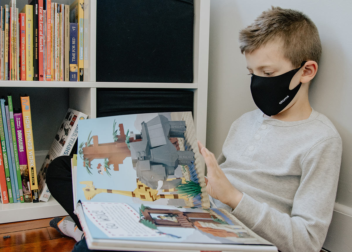 child in a mask reading a book