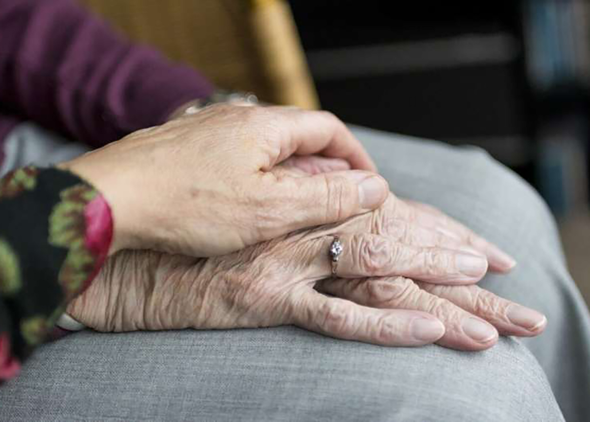 Close up of younger and elderly women holding hands