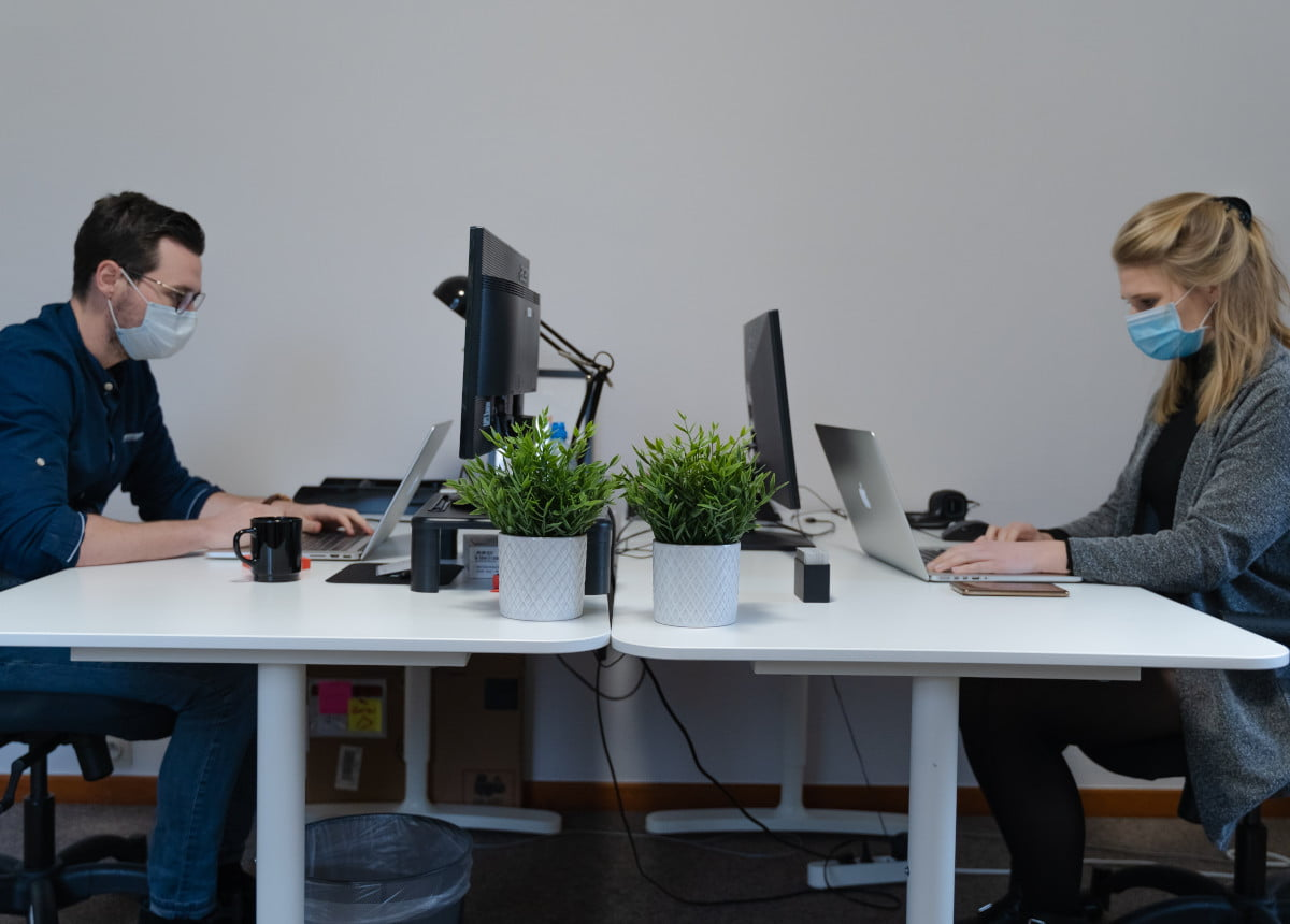 Two people working at a desk area together wearing masks