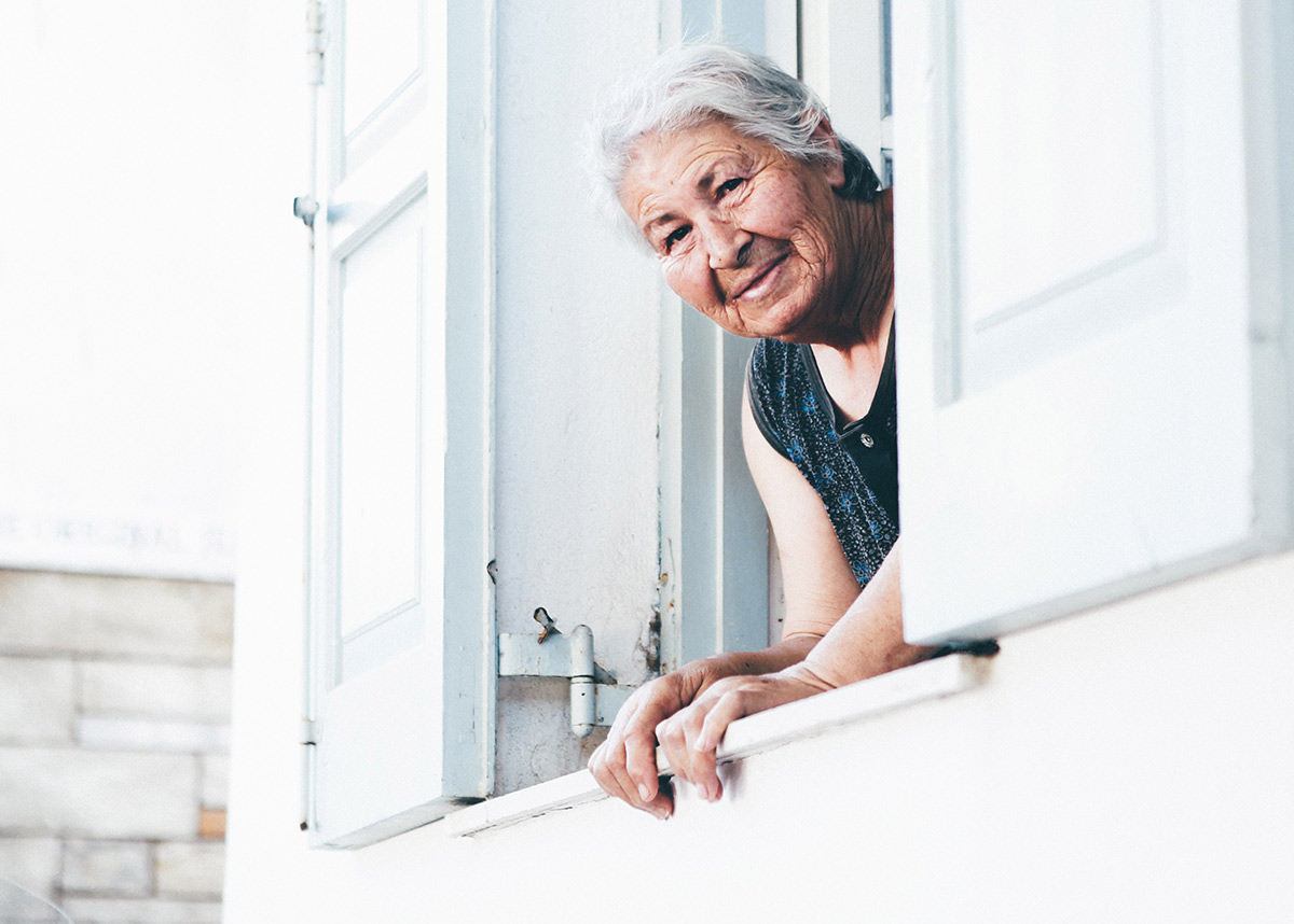 older adult woman sticking her head out of a window