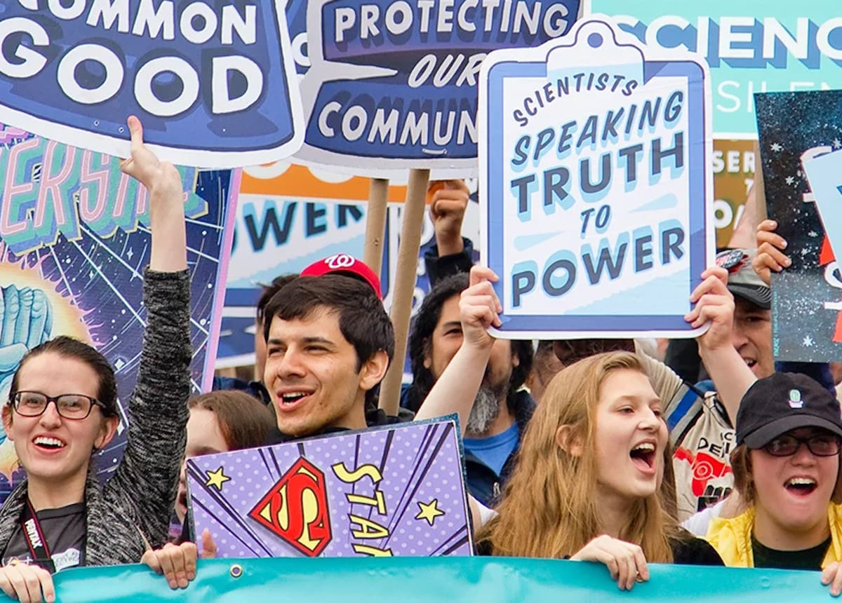 People holding up signs at a rally