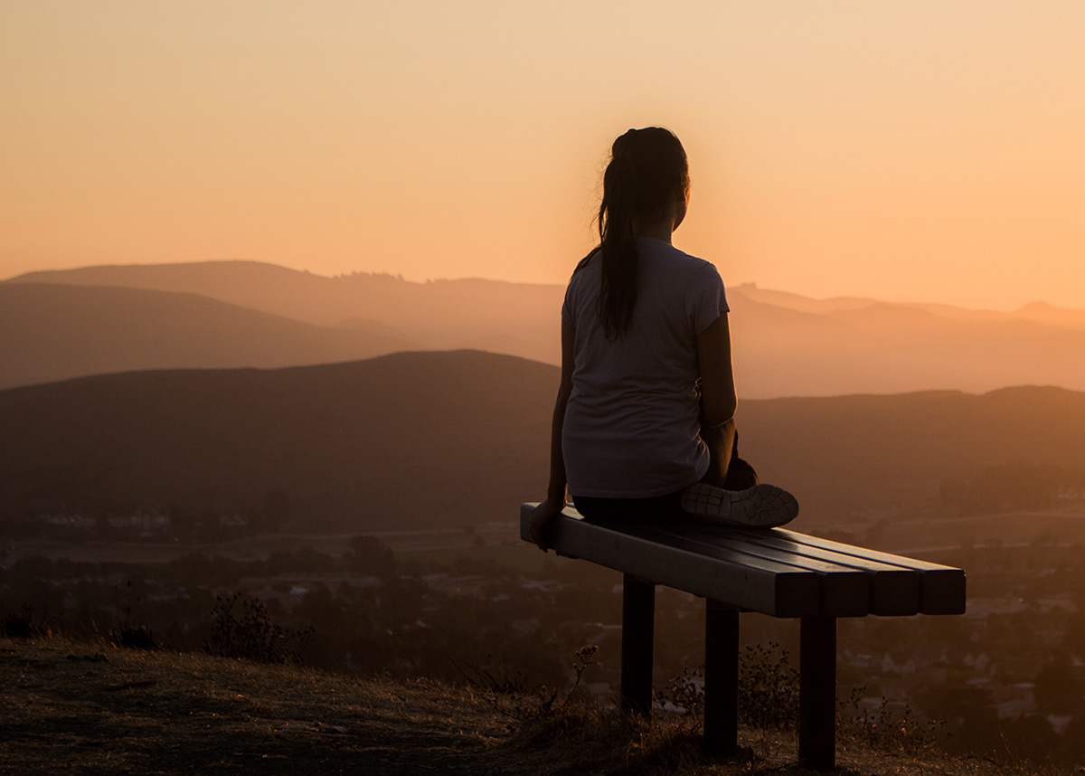 person sitting on a bench looking out over mountains