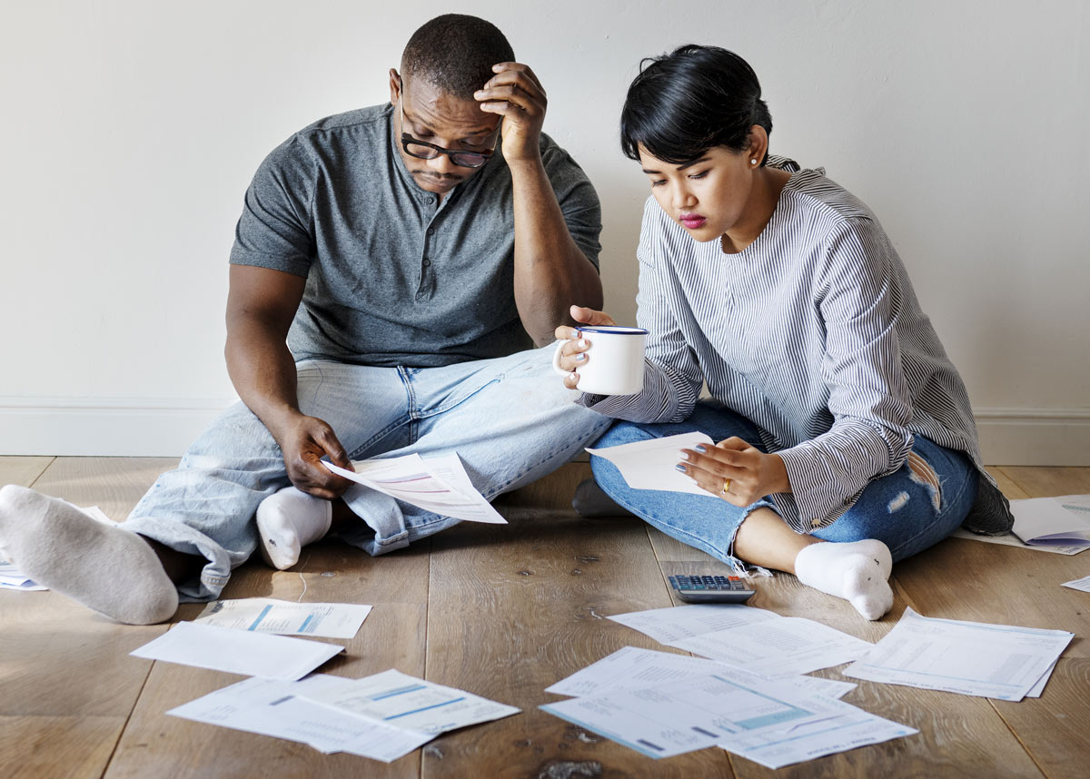 couple on floor looking at papers looking worried
