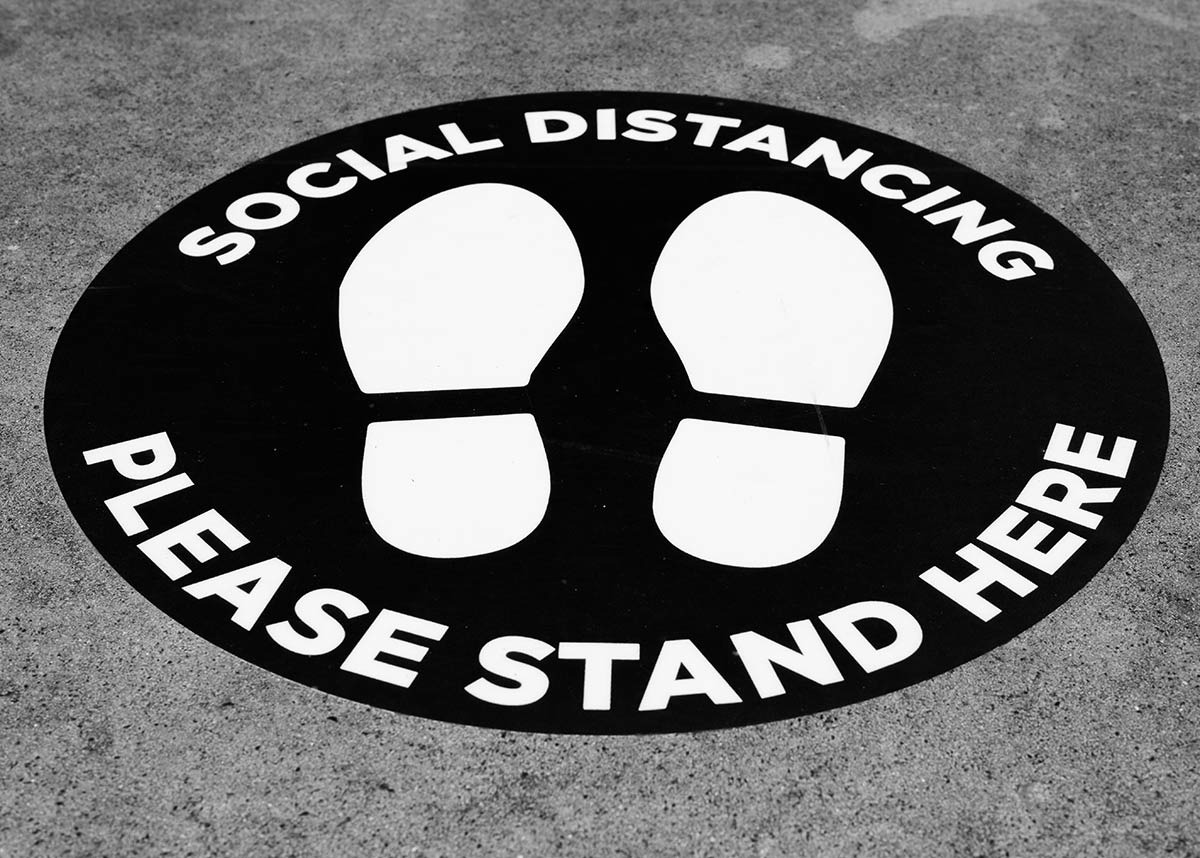 "Floor sign that reads ""social distancing please stand here"""