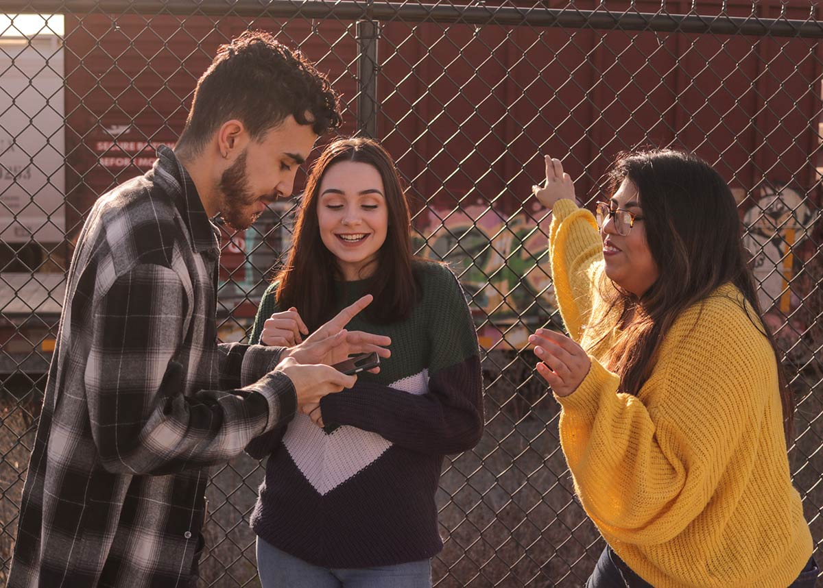 three teenagers talking against a fence