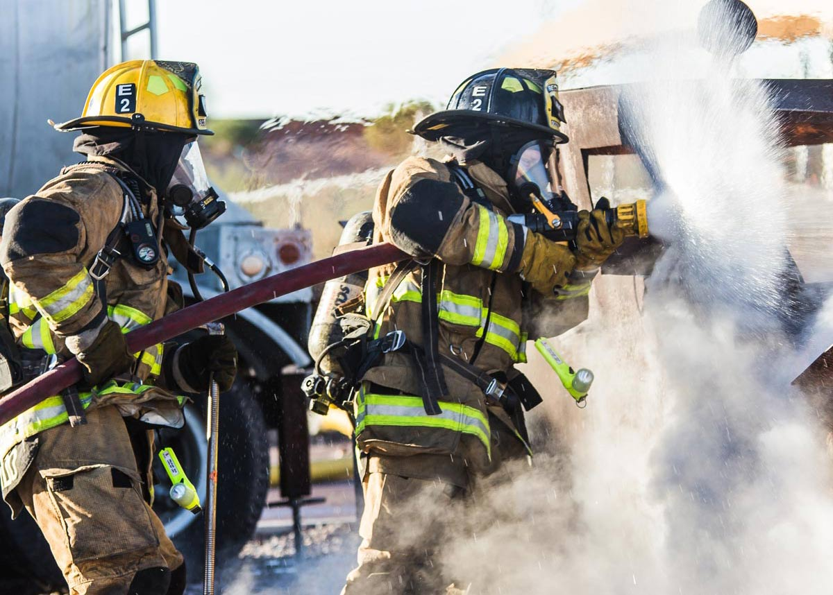 two firefighters spraying water on a fire