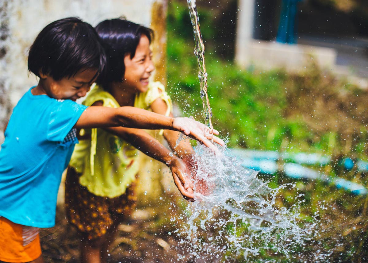 children laughing and playing in water