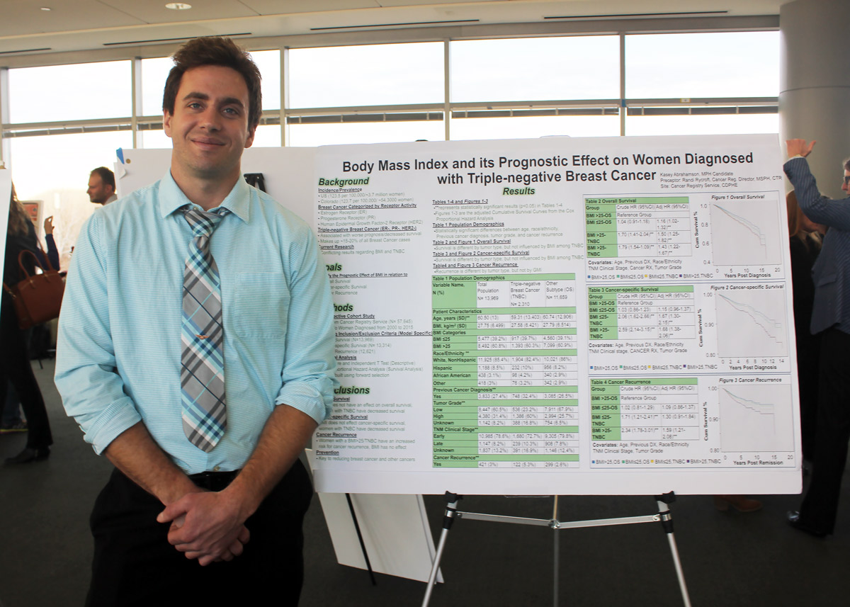 student standing next to his research poster