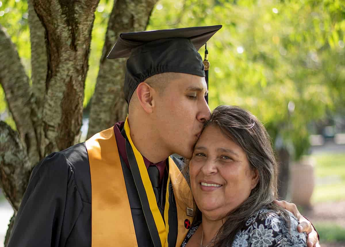 younger man with graduation cap on hugging an older woman and kissing her head