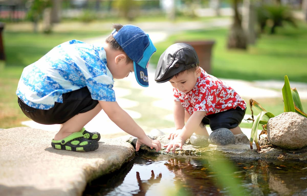 two children playing in pond