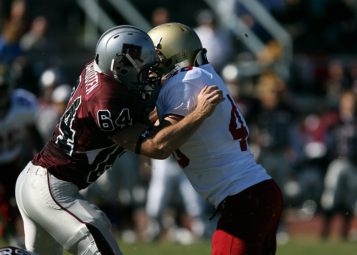 two football players wearing helmets colliding