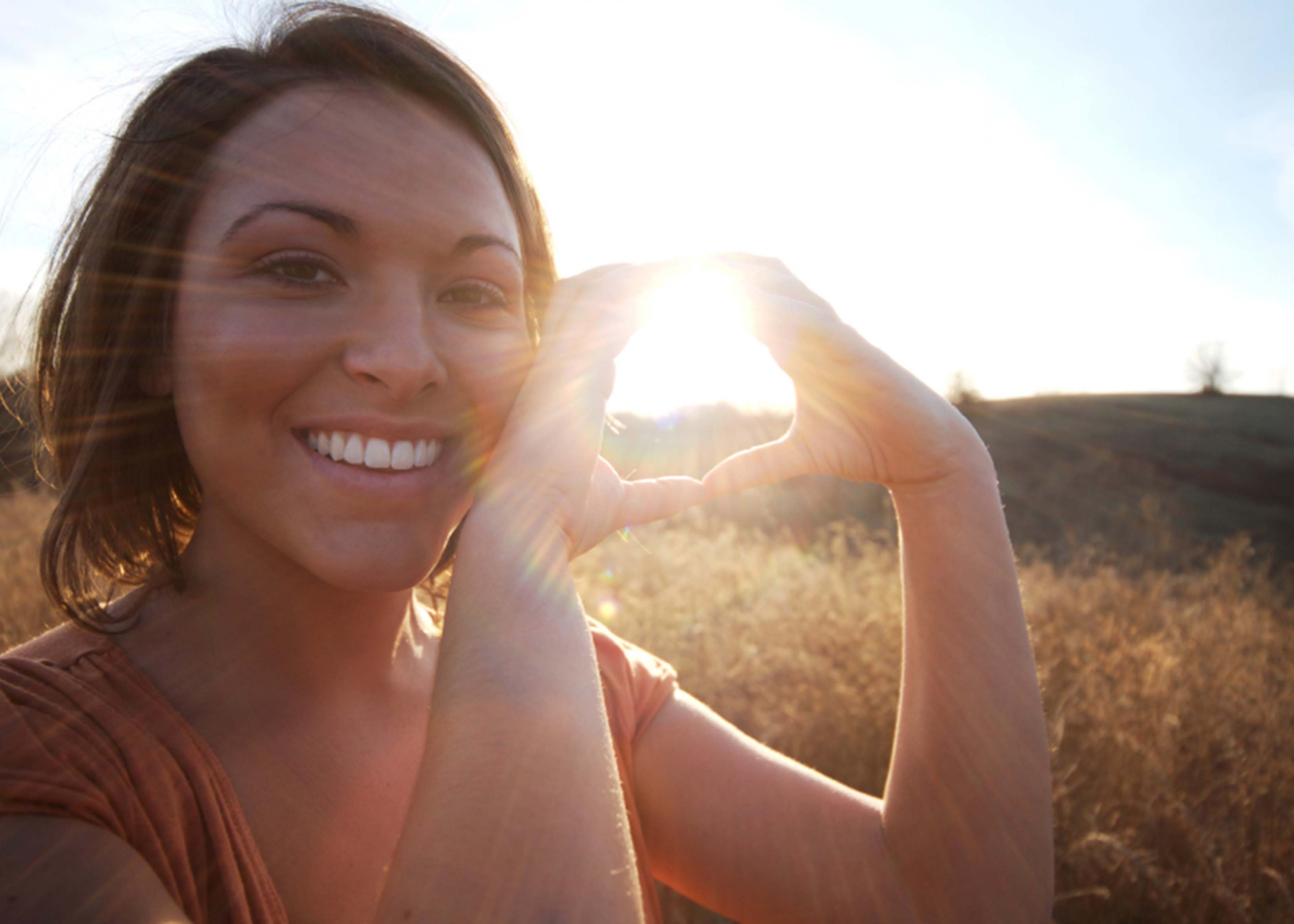 Young Native woman making a heart symbol with her hands in front of a sunset